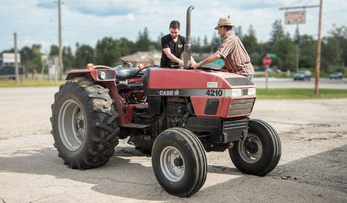 Technician teaching a mennonite farmer about preventative maintenance on his tractor