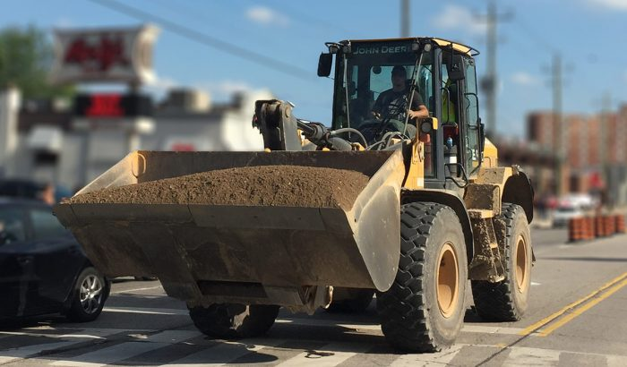 Industrial John Deere tractor delivering top soil for construction site